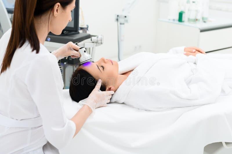 Cosmetologist concentrado que hace el tratamiento del cuidado de piel fotografía de archivo