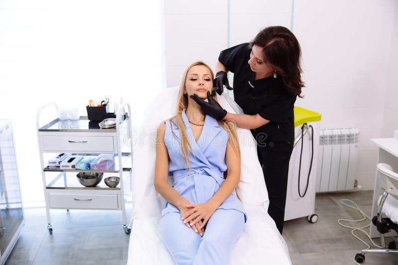 Cosmetologist de arts maakt tot gezichtsschoonheidsinjecties aan haar vrouwencliënt Mooie vrouwelijke gezicht en van cosmetologis stock fotografie