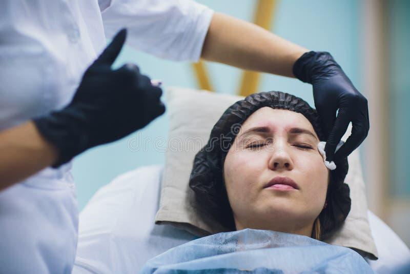 Cosmetologist de arts maakt tot gezichtsschoonheidsinjecties aan haar vrouwencliënt Mooie vrouwelijke gezicht en van cosmetologis stock foto's