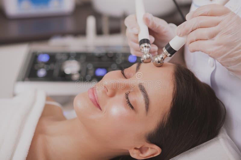 Cosmetologist de visita da jovem mulher bonita na clínica da beleza fotografia de stock
