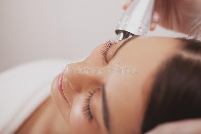 Cosmetologist de visita da jovem mulher bonita na clínica da beleza imagem de stock