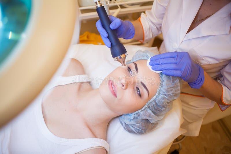 Cosmetologist del doctor que hace el balneario facial de la muchacha del masaje imagen de archivo libre de regalías
