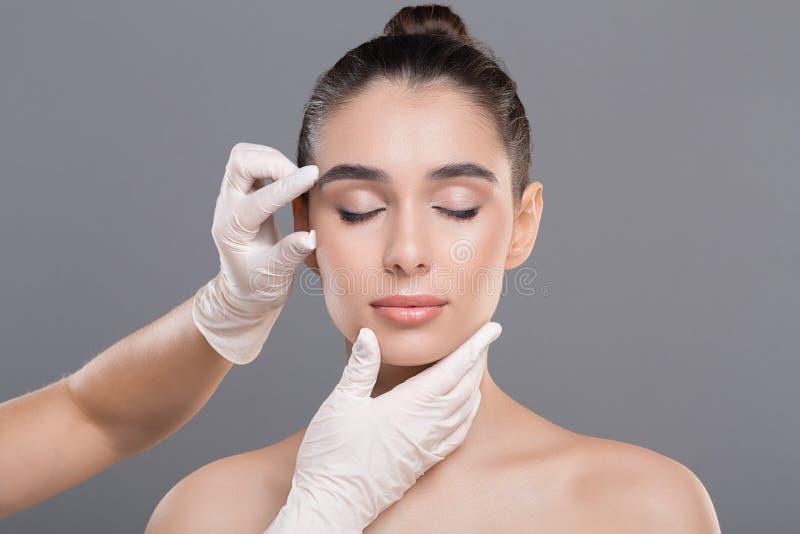 Cosmetologist, der Gesichtsfalten auf Gesicht der jungen Frau überprüft stockfotografie