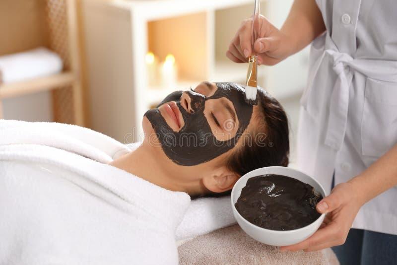 Cosmetologist, der schwarze Maske auf das Gesicht der Frau anwendet lizenzfreies stockfoto