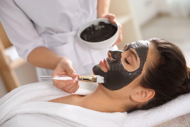 Cosmetologist, der schwarze Maske auf das Gesicht der Frau anwendet stockfoto
