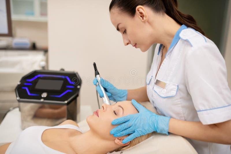 Cosmetologist, der sorgf?ltig Haut mit spezieller Laser-Ausr?stung festzieht lizenzfreies stockfoto