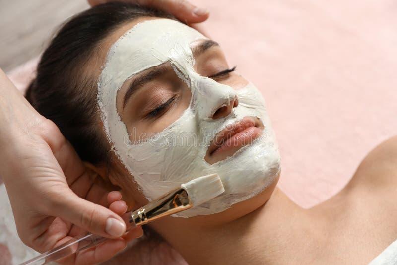 Cosmetologist, der weiße Maske auf das Gesicht der Frau anwendet stockfotos