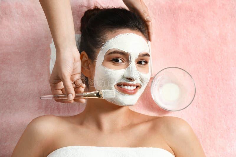 Cosmetologist, der weiße Maske auf das Gesicht der Frau im Badekurortsalon anwendet lizenzfreies stockfoto