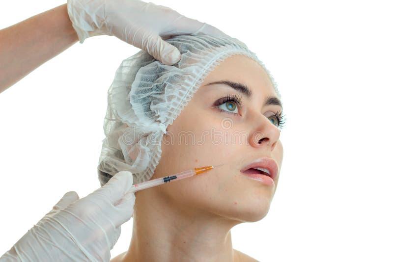 Cosmetologist die een spuit houden en spuit de injectie op het gezicht van een jong meisje in heeft close-up royalty-vrije stock afbeeldingen