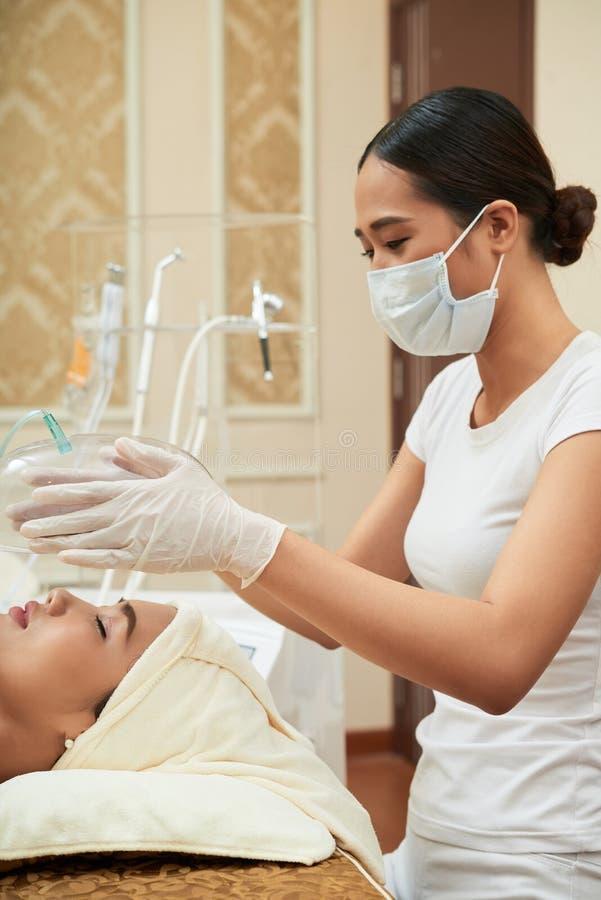 Cosmetologist die gezichtsprocedure maken stock afbeeldingen