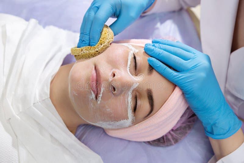 Cosmetologist die masker op gezicht van jonge vrouw in schoonheidssalon toepassen stock foto's