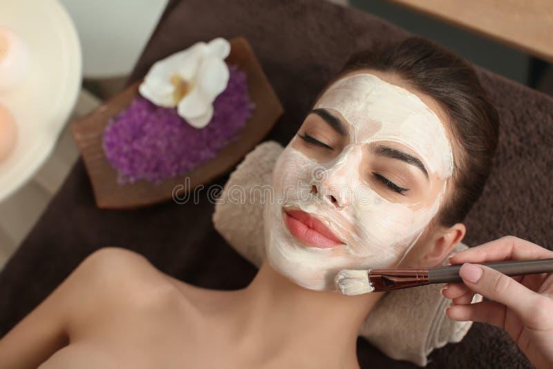 Cosmetologist die masker op het gezicht van de jonge vrouw in kuuroordsalon toepassen stock foto's