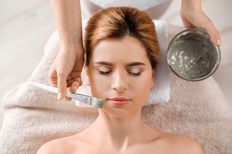 Cosmetologist die masker op het gezicht van de vrouw, hoogste mening toepast stock foto's