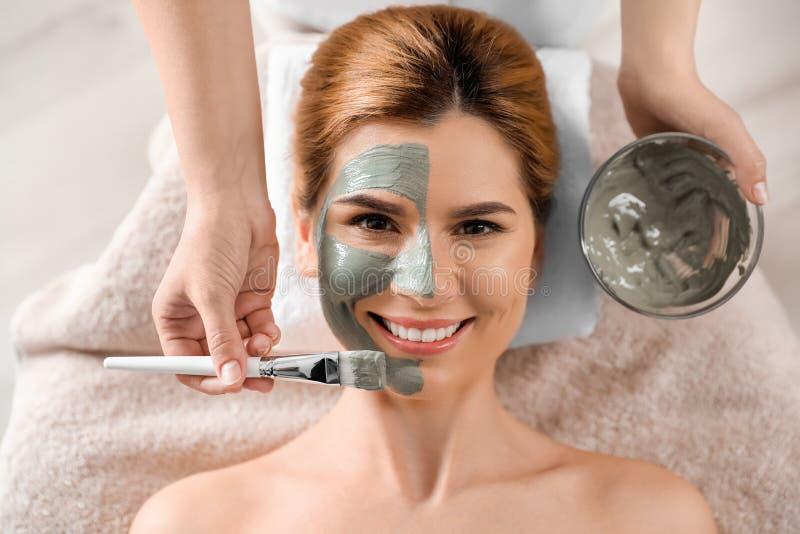 Cosmetologist die masker op het gezicht van de vrouw in kuuroordsalon toepassen royalty-vrije stock foto's