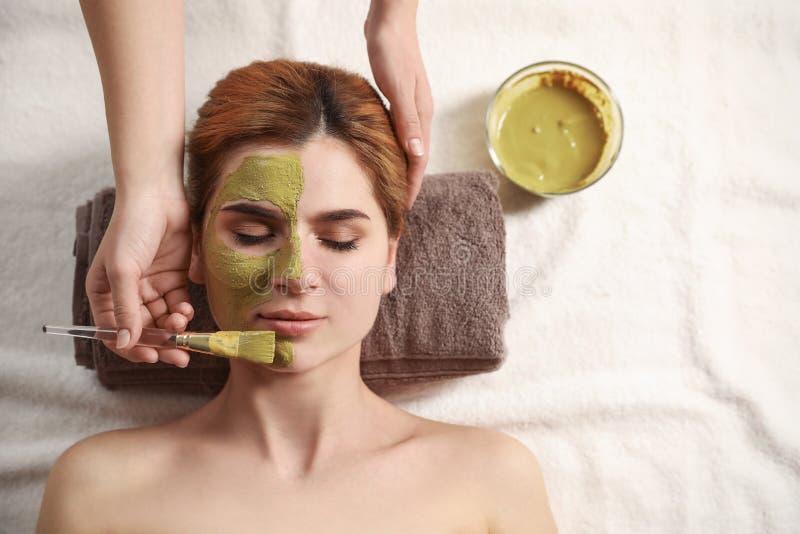 Cosmetologist die masker op het gezicht van de vrouw in kuuroordsalon toepassen, hoogste mening royalty-vrije stock fotografie