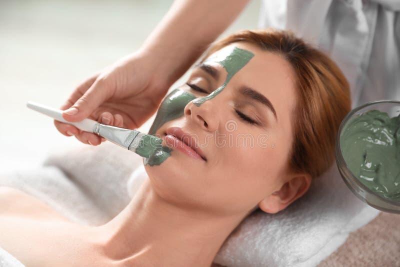 Cosmetologist die masker op het gezicht van de vrouw toepassen royalty-vrije stock afbeeldingen