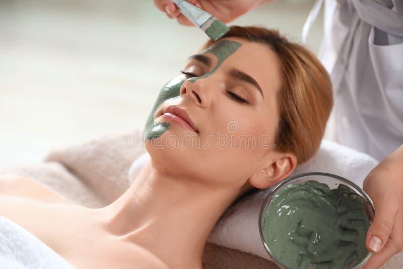 Cosmetologist die masker op het gezicht van de vrouw toepassen royalty-vrije stock foto