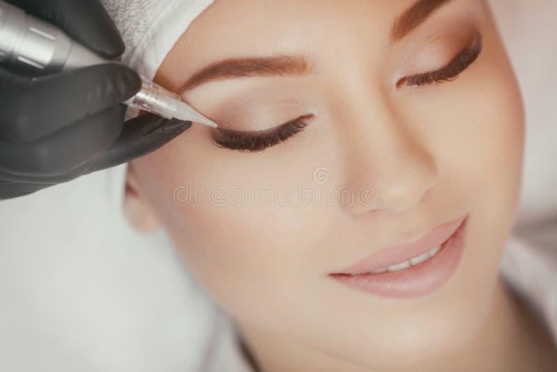 Cosmetologist die permanent omhoog bij schoonheidssalon maken maken royalty-vrije stock foto