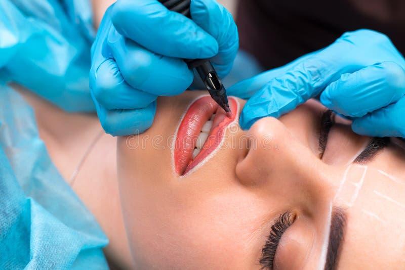 Cosmetologist die permanente make-up op vrouwen` s gezicht maken stock fotografie
