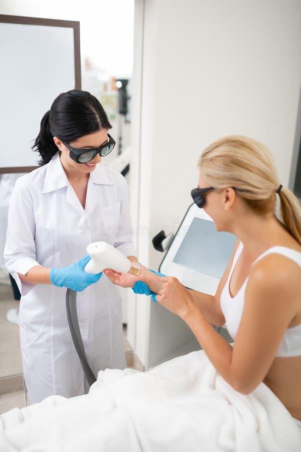 Cosmetologist die procedures voor haar glimlachende cliënt doet stock foto's