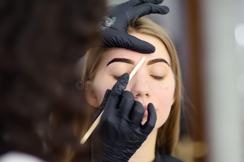 Cosmetologist die wenkbrauwenontwerp maken Aantrekkelijke vrouw die gezichtszorg krijgen bij schoonheidssalon Architectuurwenkbra royalty-vrije stock afbeeldingen