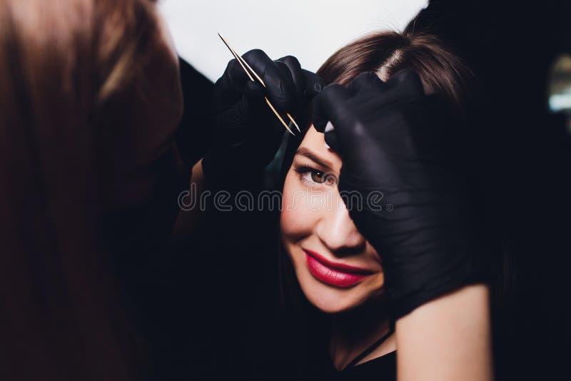 Cosmetologist die wenkbrauwenontwerp maken Aantrekkelijke vrouw die gezichtszorg krijgen bij schoonheidssalon Perfecte Architectu stock afbeeldingen