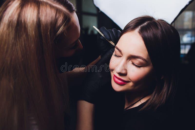 Cosmetologist die wenkbrauwenontwerp maken Aantrekkelijke vrouw die gezichtszorg krijgen bij schoonheidssalon Perfecte Architectu stock foto's