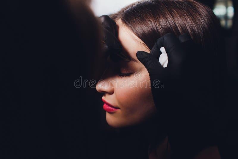 Cosmetologist die wenkbrauwenontwerp maken Aantrekkelijke vrouw die gezichtszorg krijgen bij schoonheidssalon Perfecte Architectu stock fotografie