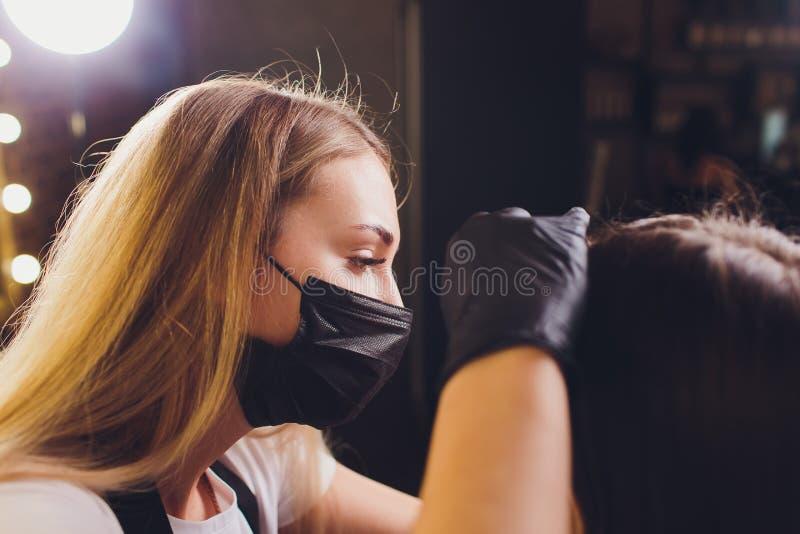 Cosmetologist die wenkbrauwenontwerp maken Aantrekkelijke vrouw die gezichtszorg krijgen bij schoonheidssalon Perfecte Architectu royalty-vrije stock foto