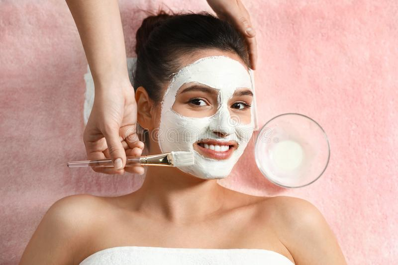 Cosmetologist die wit masker op het gezicht van de vrouw in kuuroordsalon toepassen royalty-vrije stock foto