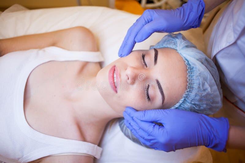 Cosmetologist do doutor que faz termas faciais da menina da massagem fotos de stock royalty free