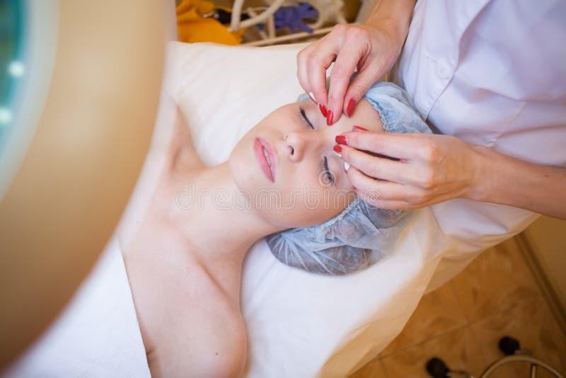 Cosmetologist do doutor que faz termas faciais da menina da massagem imagens de stock