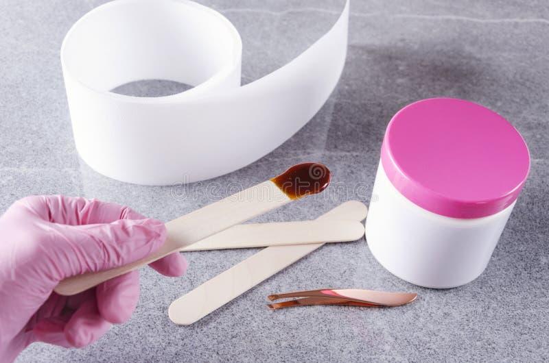 Cosmetologist en los guantes protectores rosados que sostienen el palillo con la cera para la depilación Concepto de preparació foto de archivo libre de regalías
