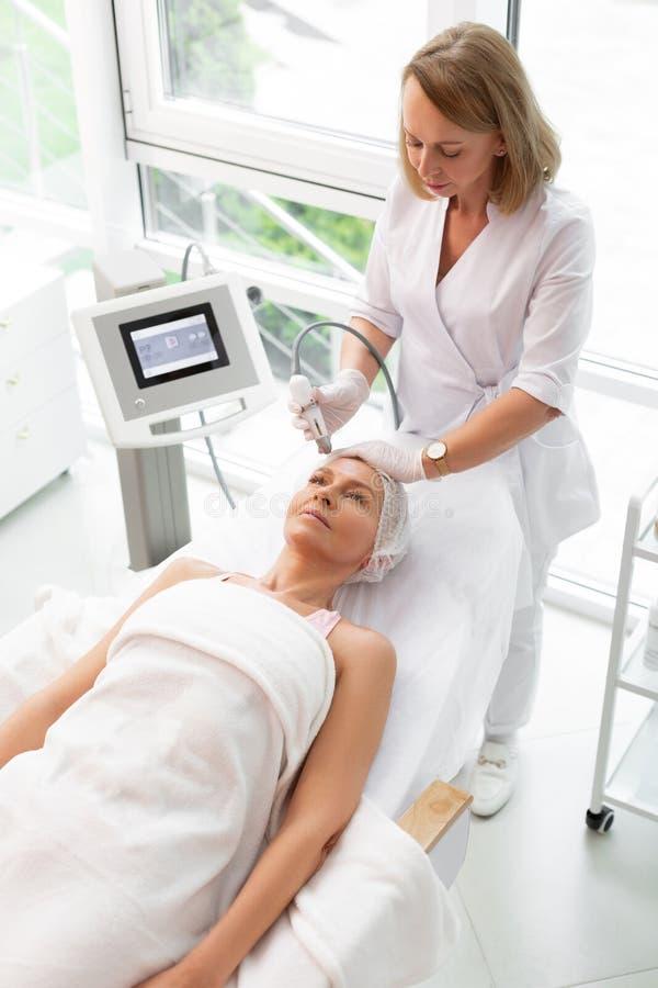 Cosmetologist especializado agradável que faz um procedimento de limpeza facial imagem de stock royalty free