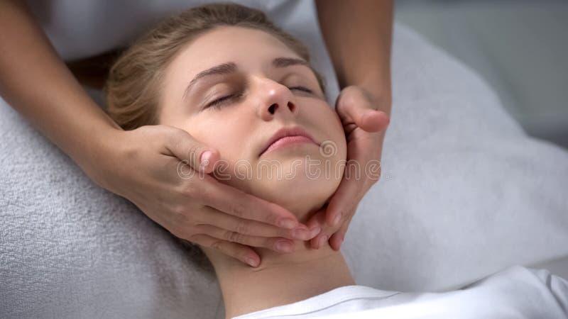 Cosmetologist experiente que faz a massagem de cara de relaxamento da menina, tratamentos imagens de stock