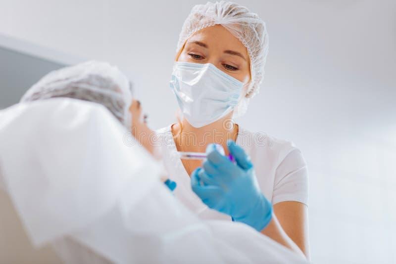 Cosmetologist féminin professionnel futé portant un masque photos libres de droits