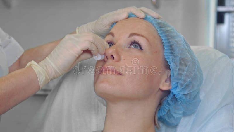Cosmetologist fêmea que limpa com cara da esponja de um cliente fêmea do salão de beleza foto de stock
