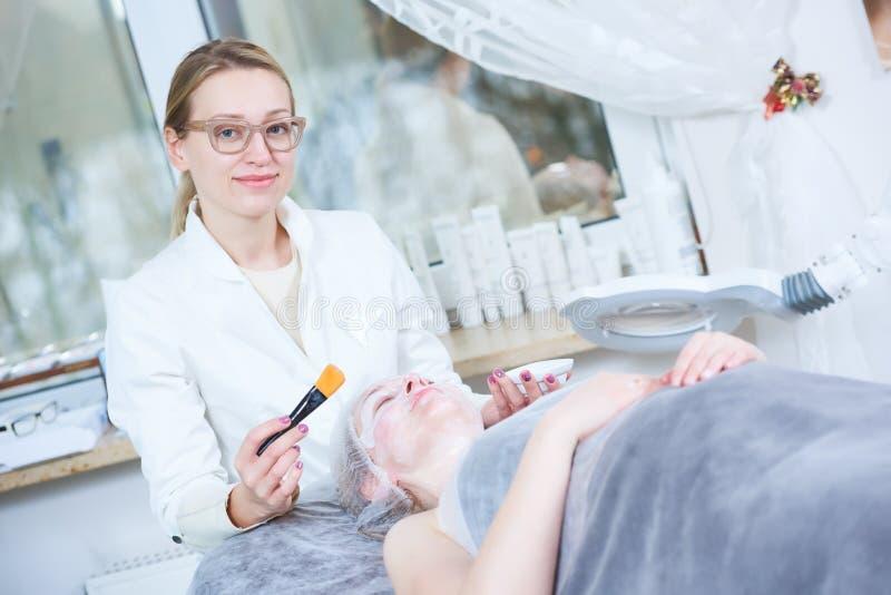 Cosmetologist för vuxen kvinnlig i cosmetologykabinett arkivfoto