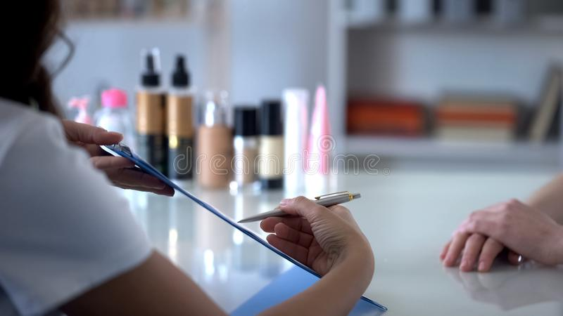 Cosmetologist filling clients card before appointing procedures, asking for sign stock photo