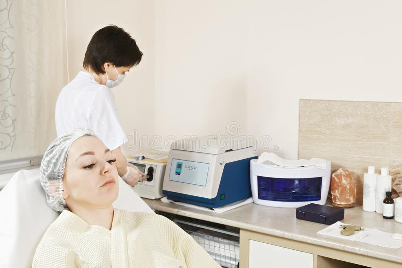 Ozone therapy. Cosmetologist fills the syringe with ozone for therapy. Patient is awaiting in chair looking sideways. This procedure is purposed to increase royalty free stock images