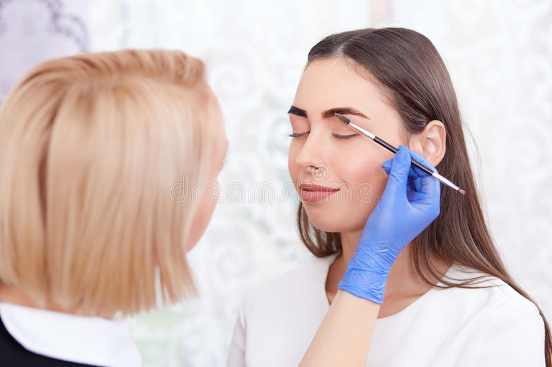 Cosmetologist in gloves making permanent eyebrows for woman. royalty free stock photography