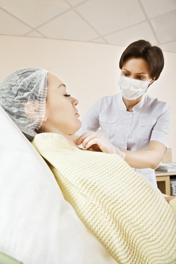 Ozone injection. Cosmetologist injecting ozone to chin. Patient is sitting in chair with closed eyes. This therapy is purposed to increase oxygen in a body royalty free stock images