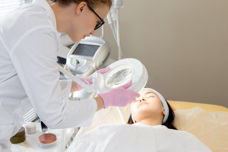 Cosmetologist Inspecting Skin stock afbeeldingen
