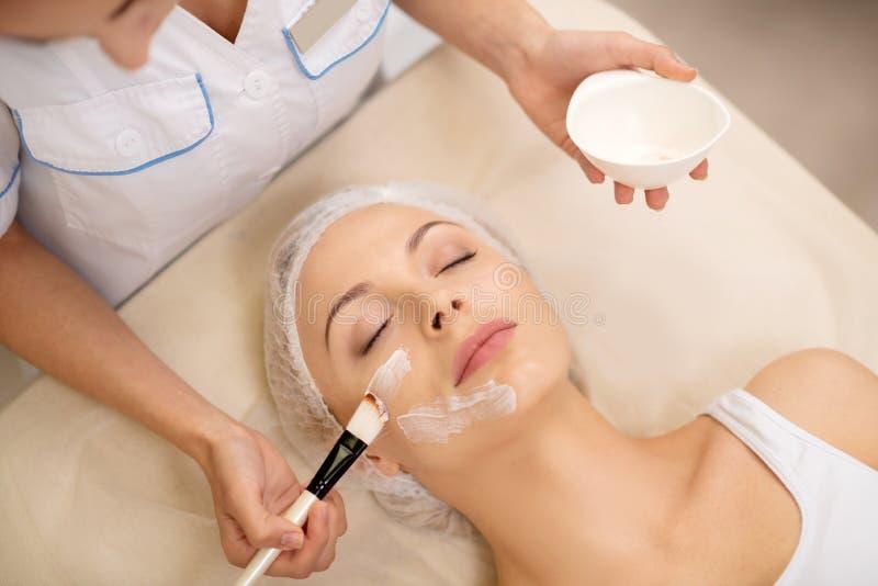 Cosmetologist k?adzenie czy?ci twarzy mask? na kliencie obrazy stock