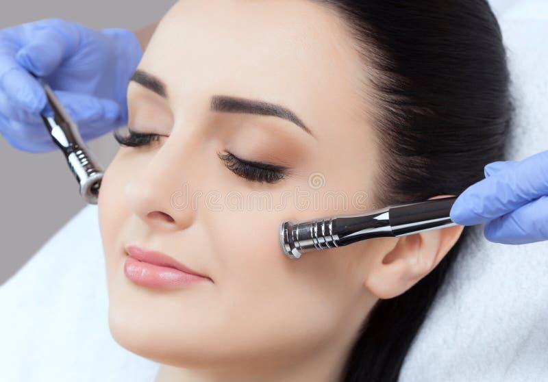 Cosmetologist maakt de Microdermabrasion-procedure van de gezichtshuid van een mooie, jonge vrouw in een schoonheidssalon stock foto's