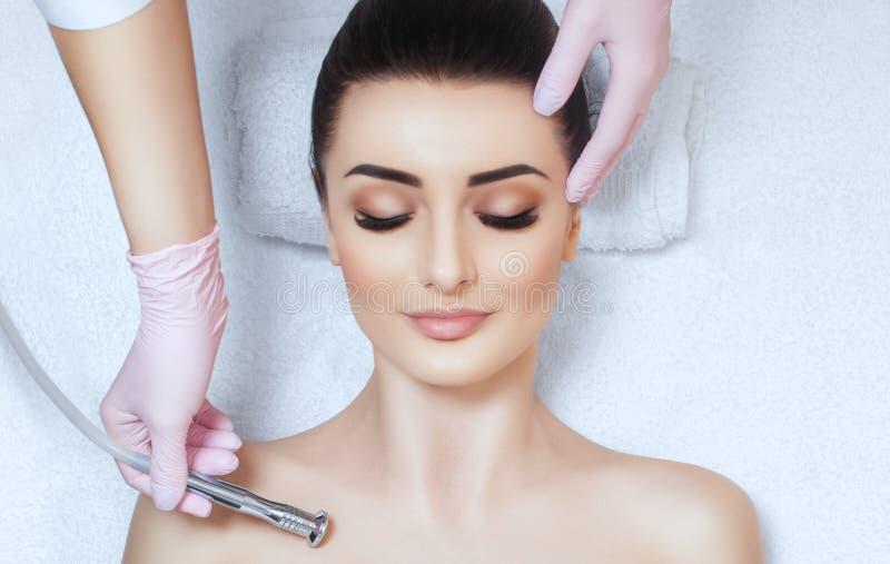 Cosmetologist maakt de procedure Microdermabrasion aangaande het sleutelbeen en de hals van een mooie, jonge vrouw in een schoonh stock foto's