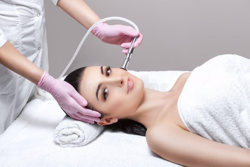 Cosmetologist maakt de procedure Microdermabrasion van de gezichtshuid van een mooie, jonge vrouw in een schoonheidssalon stock afbeelding