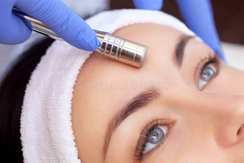 Cosmetologist maakt de procedure Microdermabrasion van de gezichtshuid van een mooie, jonge vrouw in een schoonheidssalon Cosme royalty-vrije stock foto