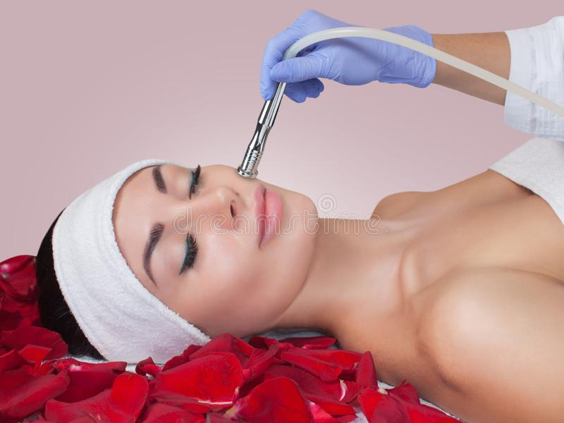 The cosmetologist makes the Microdermabrasion procedure  of the facial skin of a beautiful, young woman in a beauty salon. royalty free stock images