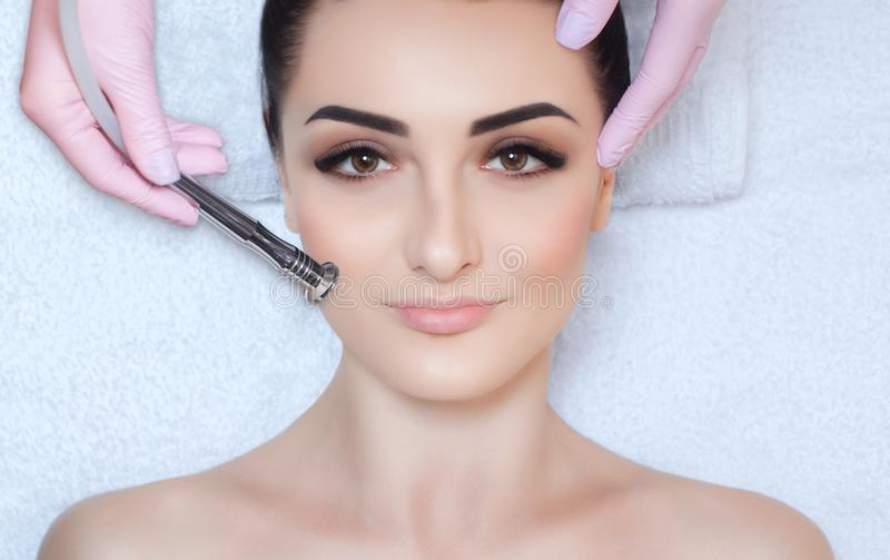The cosmetologist makes the procedure Microdermabrasion of the facial skin of a beautiful, young woman in a beauty salon stock image